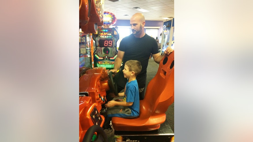 Austin Moniz, and his dad, Michael Moniz, enjoy playing a driving game during Sensory Sensitive Sunday at Chuck E. Cheese's.