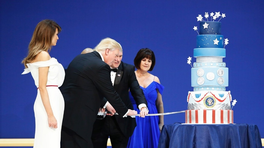 First lady Melania Trump watches as President Donald J. Trump, and Vice President Mike Pence, right,are helped by Coast Guard Petty Officer 2nd Class Matthew Babot, center, as they cut a cake at The Salute To Our Armed Services Inaugural Ball Friday, Jan. 20, 2017, in Washington. Karen Pence watches at right. (AP Photo/Alex Brandon)