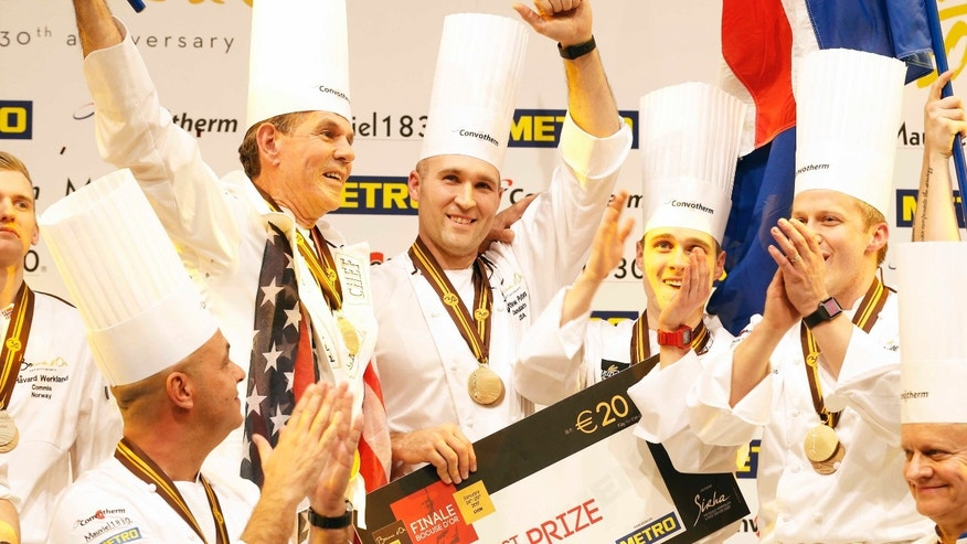 "Mathew Peters of Team USA, center, celebrates on the podium with teammates after winning the ""Bocuse d'Or"" (Golden Bocuse) trophy, in Lyon, central France, Wednesday, Jan. 25, 2017. The contest, known as the Olympics of the food world, was started in 1987 by Lyon chef Paul Bocuse to reward young international culinary talents."