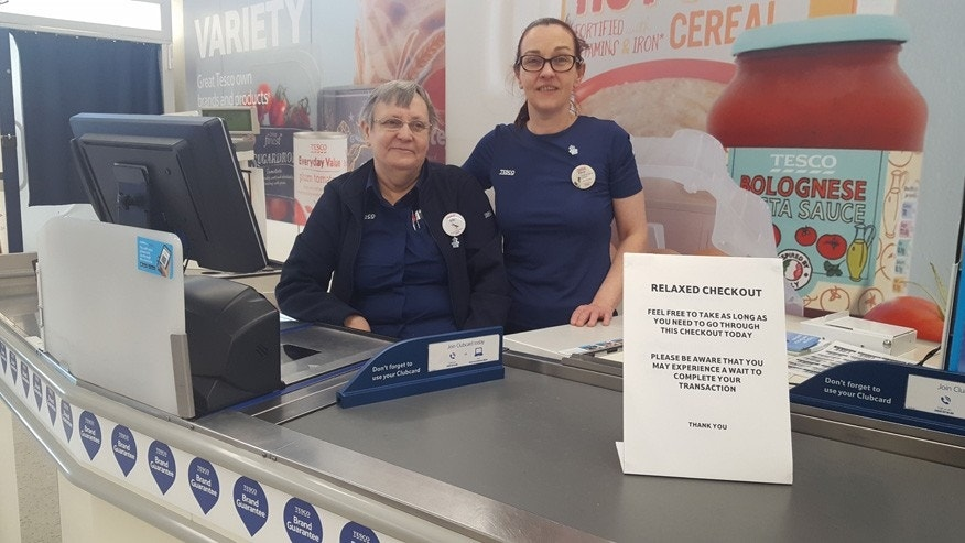 Tesco employees Iris Beveridge and Kerry Speed are seen behind the relaxed checkout lane.