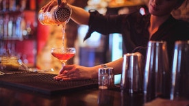Close-up of a young female bartender pouring cocktail in a nightlife cocktail bar. Selective focus. Focus on foreground.