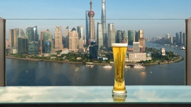 Beer and foam beer on table in rooftop bar with Shanghai skyscraper in background in Shanghai, China. Viewpoint of Shanghai, China.