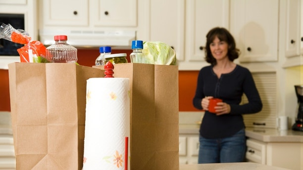 Woman in the kitching with cup of coffee, she is looking at the grocery bags to be unloaded that are on the counter.