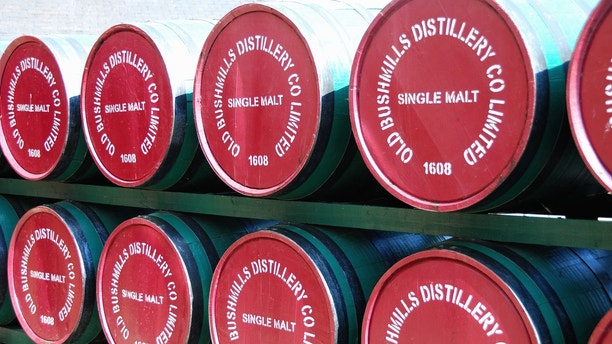 Bushmills, County Antrim, Northern Ireland - June 9, 2013: Barrels of Old Bushmills Irish Whiskey are stacked at the entrance to the Distillery. Founded in 1743 it hosts over 120,000 visitors a year.