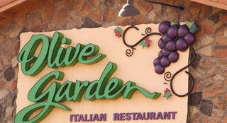 """Westminster, U.S.A.  -  April 15, 2012: The exterior of a Olive Garden Restaurant with a large sign. The Olive Garden Sign is on the  rock exterior of the building. Olive Garden is in green lettering, and Italian Restaurant is in purple."""