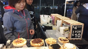 This April 22, 2017 photo shows vendors at the Queens Night Market in New York City's Corona, Queens, neighborhood, selling Indonesian coconut cake snacks with various toppings. The market showcases about 50 food vendors, many of them immigrants selling examples of cuisine from their home countries, and is modeled on traditional night markets found in Asia. Similar night markets are popping up in other cities around the U.S.(AP Photo/Beth J. Harpaz)