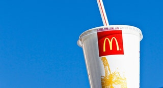 """Cape Town, South Africa - June 21, 2011: A McDonald's soft drink container sits on the roof of a car outside a branch of the multinational fast-food chain in Cape Town's southern suburbs."""