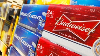 Anheuser Busch's Budweiser and Bud Light Beer can be seen on display at a new Wal-Mart store in Chicago, January 24, 2012. The store will open on January 25, and it will be Wal-Mart's largest outlet in Chicago. REUTERS/John Gress (UNITED STATES - Tags: BUSINESS FOOD) - RTR2WT10