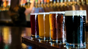 A flight of 4 craft beers lined up on the bar.
