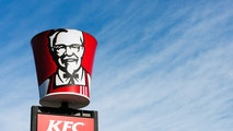 """Cape Town, South Africa - June 21, 2011: A KFC bucket bearing the image of founder Colonel Harland Sanders is placed above a Drive-thru sign at a suburban KFC franchise in Cape Town."""
