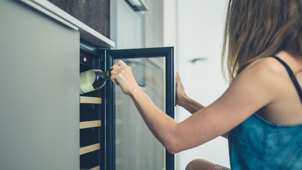 A young woman is getting a bottle of white wine from her wine cooler at home