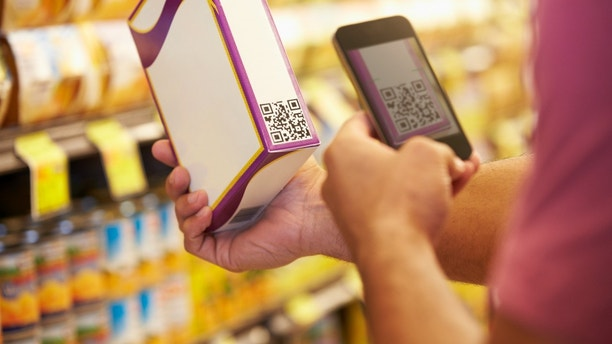 Man Scanning Voucher Code In Supermarket With Mobile Phone                        -NOTE TO EDITOR-            -PHONE SCREEN AND BARCODE-                  - CREATED FOR SHOOT-