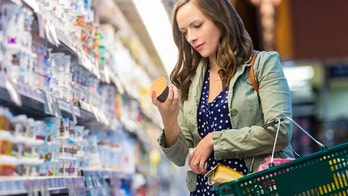 Woman at grocery store reading food labels while holding her shopping basket.