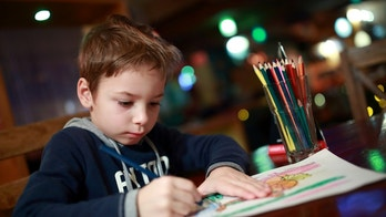 Boy drawing at table in a cafe