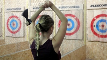 """A participant prepares to throw an axe in the new opened axe-throwing venue """"Les Cognees"""" (Axes) in Paris, France, October 26, 2017. Picture taken October 26, 2017.   REUTERS/Charles Platiau - RC199445D000"""