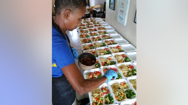 Granny Gloria Lewis, a kind-hearted waitress spends her weekends whipping up fresh meals for the homeless in her community and has dished out 75,000 DINNERS from her own kitchen.  See SWNS story NYMEALS; Granny Gloria Lewis, 54, spends her weekends making 225 fresh dinners and 180 breakfasts from her two-stove, four-fridge kitchen after years of living on the brink of homelessness in her low-income job. Gloria, who moved to the US from Barbados in 1987, spends $700 on groceries every weekend to make dozens of home-cooked meals for those in need. Every Sunday the charitable mom-of-two preps giant trays of chicken parmesan, spaghetti and meatballs, barbeque chicken and ribs, along with fresh veggies and rice to help those on the street. Waitress Gloria, who also works full time, spends her Mondays in downtown Fort Lauderdale where hundreds of people gather for her fresh meals every week.