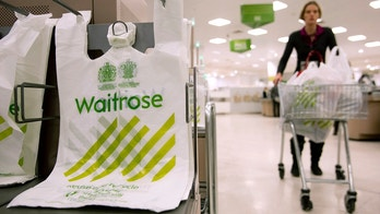 A shopper passes by branded bags in the Canary Wharf store of Waitrose in London. January 23, 2013. Waitrose outperformed bigger rivals Tesco, Sainsbury's and Morrisons at Christmas and market research group Kantar Worldpanel said last week its market share in the festive trading period was 4.9 percent - a new high. Picture taken January 23, 2013.  REUTERS/Neil Hall (BRITAIN - Tags: BUSINESS FOOD) - LM1E91P0JPC01