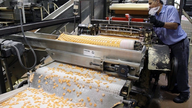 FILE - In this Jan. 14, 2009 file photo, Sweethearts candy drop onto a conveyor belt as they are manufactured at the New England Confectionery Company in Revere, Mass. Four bidders are vying to buy the bankrupt manufacturer of Necco Wafers, Sweethearts and other iconic candies. A bankruptcy auction is scheduled for Wednesday, May 23, 2018. (AP Photo/Charles Krupa, File)