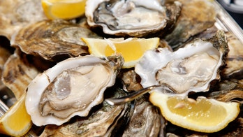 Close up of a platter of oysters with lemon wedges