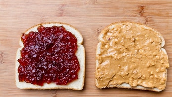 Simple peanut butter and jelly sandwich with strawberry jam and chunky peanut butter on white bread, separated and placed on a bamboo cutting board with soft natural window light.