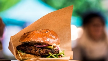 Close up image of a vegan burger on a market stall at the famous Borough Market in London, UK. Extremely shallow depth of field with lights and the commotion of the busy market blurred out of focus in the background. Horizontal colour image with copy space.