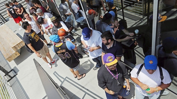 Los Angeles Lakers fans wait in line around noon for promised free pizza that will be handed out between 2 and 5 p.m. at Blaze Pizza, a restaurant chain NBA basketball player LeBron James was an original investor in, Tuesday, July 10, 2018, in Culver City, Calif. James had hinted that he might appear at the location today. (AP Photo/Reed Saxon)