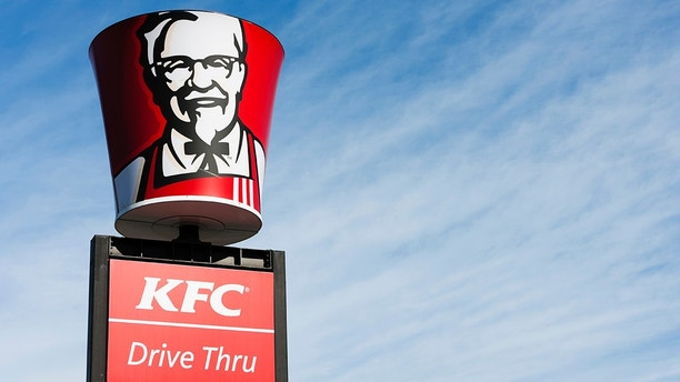 """""""Cape Town, South Africa - June 21, 2011: A KFC bucket bearing the image of founder Colonel Harland Sanders is placed above a Drive-thru sign at a suburban KFC franchise in Cape Town."""""""