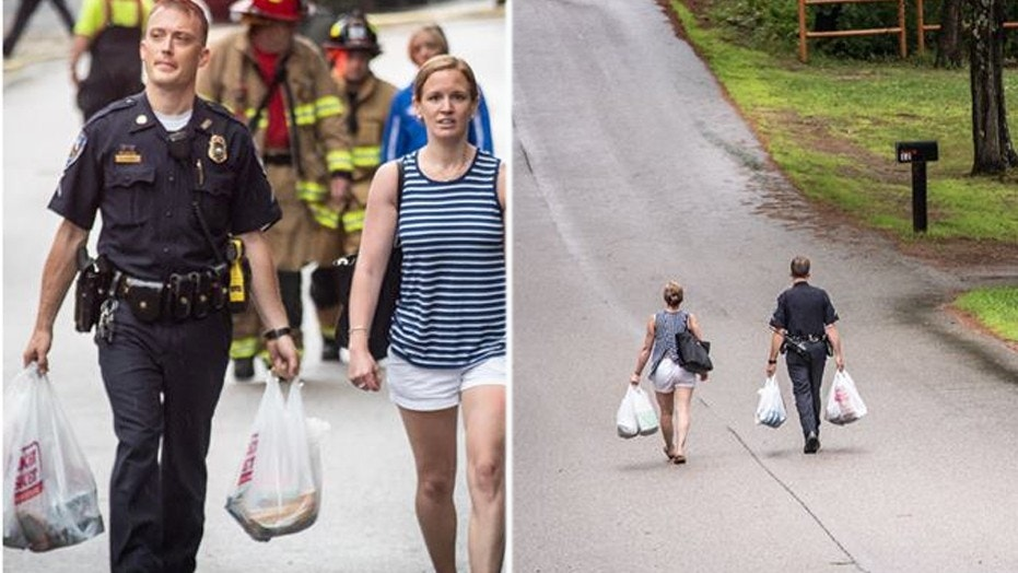 Police officer goes the extra mile, carries woman's groceries uphill after fire