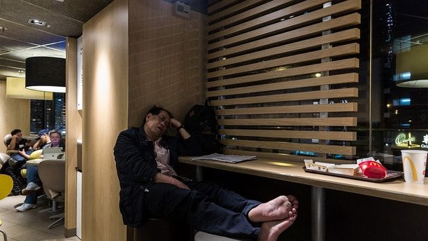 "In this picture taken early on April 9, 2016, a man (C) sleeps next to his backpack at a McDonalds outlet in the Kowloon district of Hong Kong. / AFP / Anthony WALLACE / To go with ""HongKong-social-politics-homeless"" FEATURE by Laura Mannering        (Photo credit should read ANTHONY WALLACE/AFP/Getty Images)"