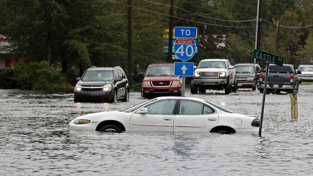 Cars try to navigate a flooded road leading to Interstate 40 in Castle Hayne, N.C., after damage from Hurricane Florence cut off access to Wilmington, N.C., Sunday, Sept. 16, 2018. (AP Photo/Chuck Burton)