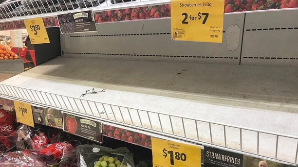In this Sept. 14, 2018, photo, empty shelves, normally stocked with strawberry punnets, are seen at a Coles Supermarket in Brisbane. Public fears about sewing needles concealed inside strawberries on supermarket shelves have spread across Australia and New Zealand as growers turn to metal detectors and the Australian government launches an investigation to restore confidence in the popular fruit.(Dan Peled/AAP Image via AP)