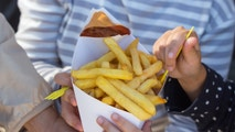 French fries with ketchup and curry sauce in the white box on woman and kid hands