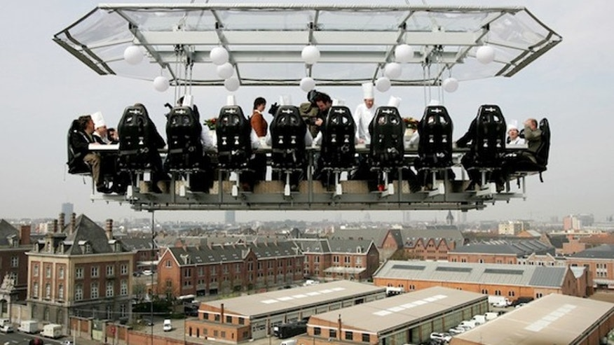 BEST QUALITY AVAILABLE A group of 22 Belgian chefs enjoy a plate of oysters at a table suspended by crane 50 metres above Brussels traffic, April 24, 2006.  REUTERS/Francois Lenoir