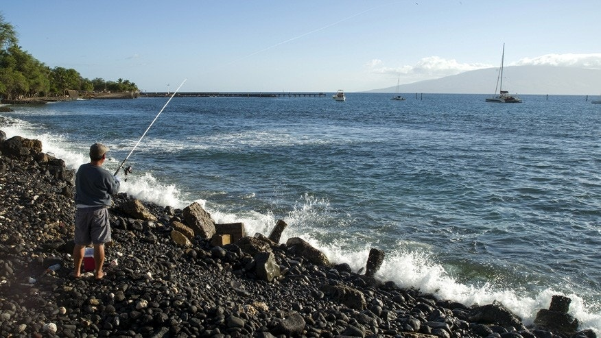A fisherman casts his reel in waters off the coast of Maui, Hawaii.