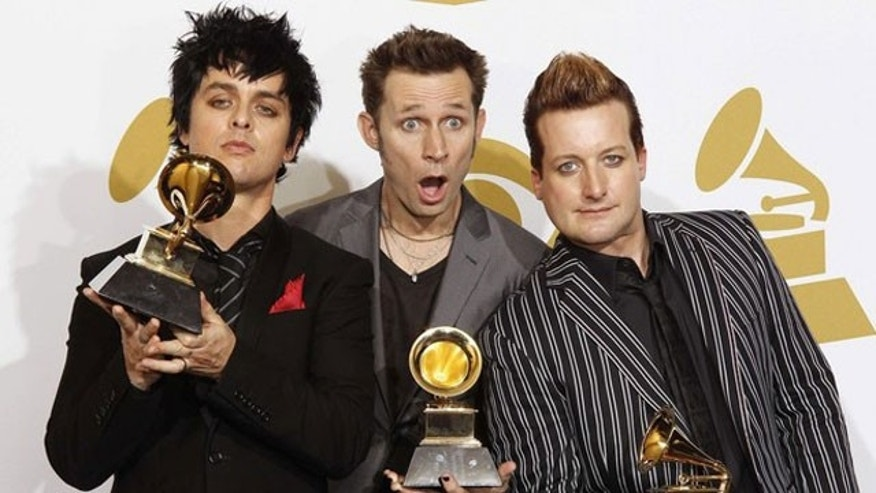 Billie Joe Armstrong, left, and Tre Cool, far right, of Green Day, are known for wearing eye make-up.