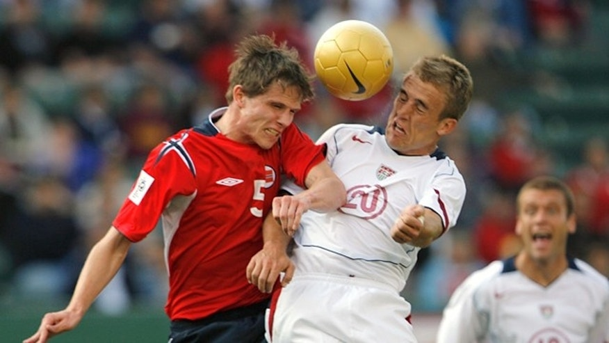 Taylor Twellman (C) of the U.S. and Norway's Erlend Hanstveit jump for the ball during their soccer match in Carson, California January 29, 2006.