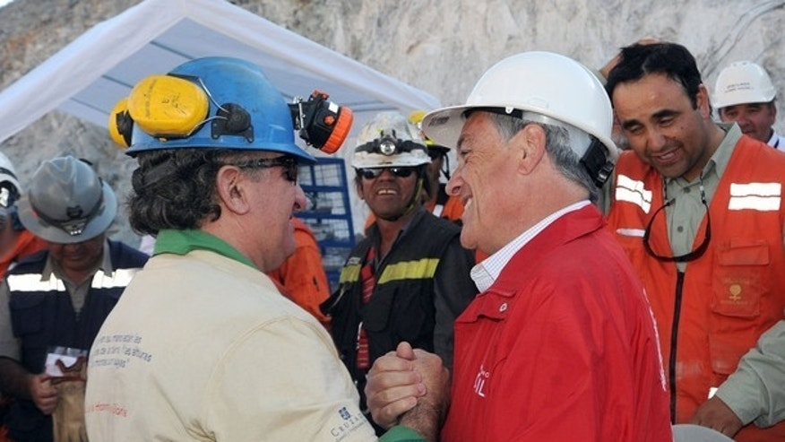 Trapped miner Jose Henriquez (L) is greeted by Chile's President Sebastian Pinera after reaching the surface to become the 24th to be rescued from the San Jose mine in Copiapo October 13, 2010.