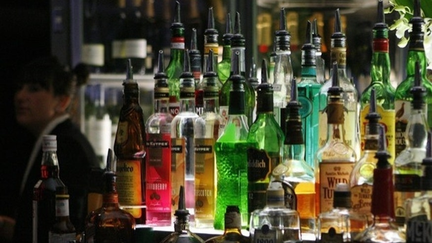 A bartender walks next to liquor bottles in a bar in central Sydney May 11, 2009. The Australian government will announce on May 12 what is the most keenly watched national budget in years, as the country heads for a recession, unemployment rises and rumours swirl of a possible early general election. The government is expected to increase taxes for cigarettes and alcohol in this budget.  REUTERS/Daniel Munoz (AUSTRALIA POLITICS BUSINESS IMAGES OF THE DAY)