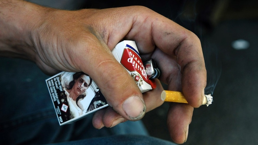 A man holds a cigarette and a pack with a picture of a cancer patient printed on it at a street in Montevideo, Uruguay, Monday Nov. 15, 2010. Philip Morris International Inc., the world's second-biggest cigarette company, is pursuing a claim before World Bank arbitrators alleging that Uruguay is violating its trade agreement by requiring that anti-smoking warnings cover 80 percent of cigarette packages. (AP Photo/Matilde Campodonico)