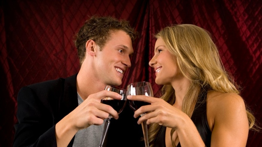 Attractive couple toasting with wine