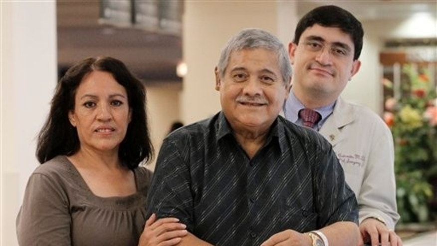 In this photo taken Sept. 22, 2010 in Chicago, Dr. Juan Carlos Caicedo, a transplant surgeon and director of Northwestern University's Hispanic Transplant program, poses with liver transplant patient Estanislao Garcia and his wife Adelita Garcia. Garcia received his new liver at Northwestern last March which boasts the only known transplant program in the United States conducted entirely in Spanish and tailored to the unique needs of Hispanic patients. (AP Photo/M. Spencer Green)