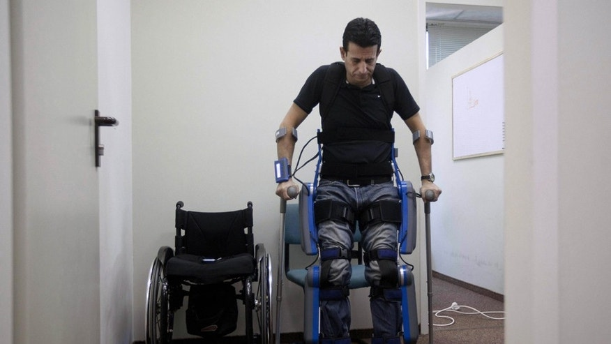 "Nov. 18: Radi Kaiuf, wounded and left paralyzed during his military service, gets up while strapped to ""ReWalk,"" a device helping paralyzed patients stand and walk, in the northern Israeli town of Yokneam."