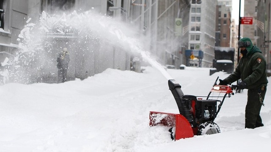 A worker removes snow from a sidewalk in New York City after a blizzard hit the area on December 27, 2010.