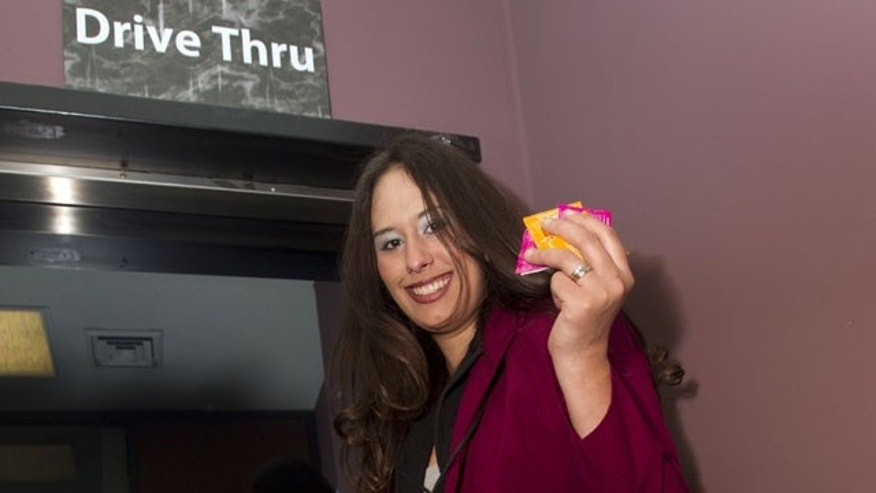 Gabrielle DeSilva, owner of Pleasures, holds condoms at her store in Huntsville, Ala.