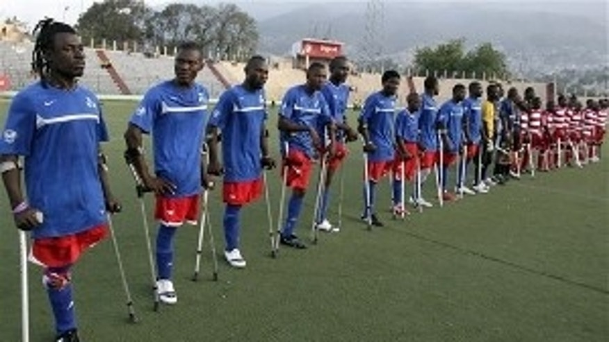 Players belonging to the local Zaryen team, left, and Haiti's unofficial national amputee soccer team line up prior to a friendly match at the national stadium in Port-au-Prince, Haiti, Monday Jan 10, 2011.