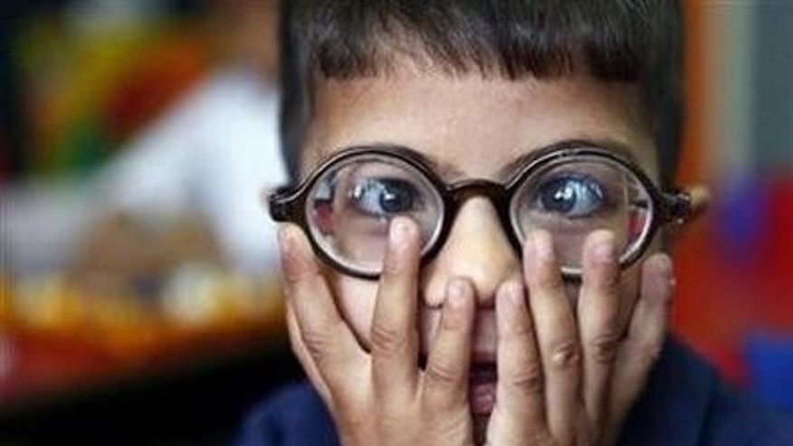 A visually impaired boy wears glasses in this file photo. REUTERS/Yannis Behrakis