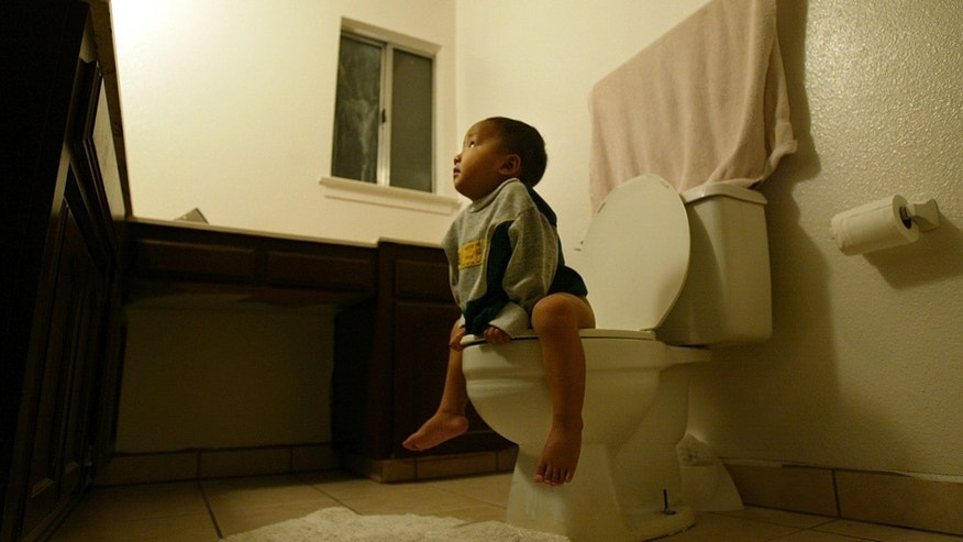 FRESNO,CA.- DECEMBER 11: Kou Vang, age 2, sits on the toilet, learning a new skill at the Vang's home December 11,2004 in Fresno, California. The Vang family is getting adjusted to life in America after their arrival on August 23 settling in Fresno, California. The Vangs are among thousands of Hmong refugees who fled Laos for Thailand 30 years ago and were part of the current U.S government resettlement program for up to 15,000 Hmong. They now rent a 3 bedroom home, living on $1,400 a month from Welfare and $700,00 in food stamps for the family of eleven.  (Photo by Paula Bronstein/Getty Images)
