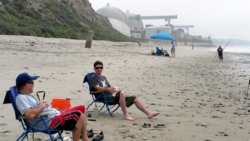 Beachgoers sit near the San Onofre Nuclear Generating plant in north San Diego County, California.