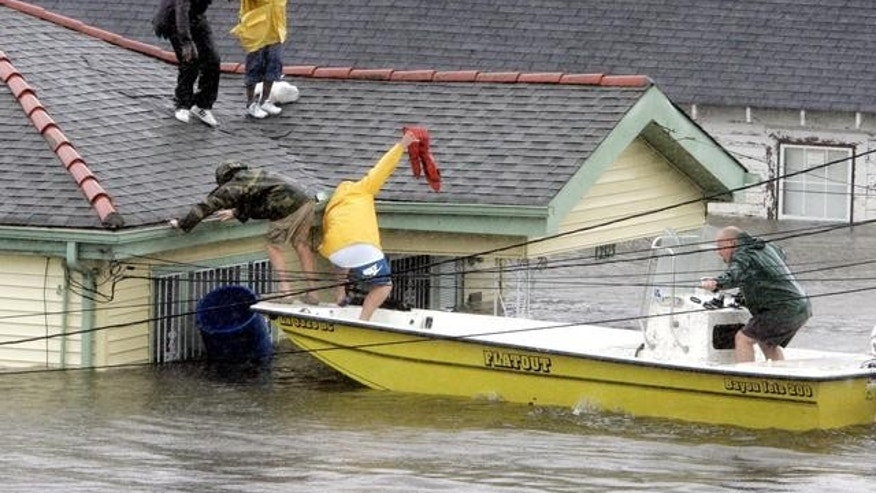 **RESENDING TO CORRECT SPELLING OF DOROTHY**  Bryan Vernon and Dorothy Bell are rescued from their  rooftop after  Hurricane Katrina hit, causing flooding in their New Orleans neighborhood,  Monday Morning, Aug. 29,  2005. Officials called for a mandatory evacuation of the city, but many residents remained in the city.  (AP Photo/Eric Gay)