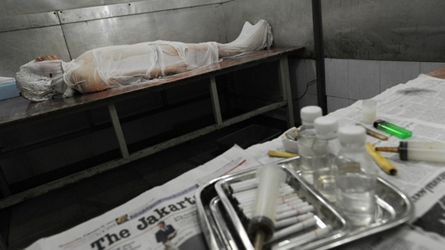 An patient, wrapped with a wet cloth on a table at the Griya Balur clinic in Jakarta, undergoes treatment for cancer using tobacco.